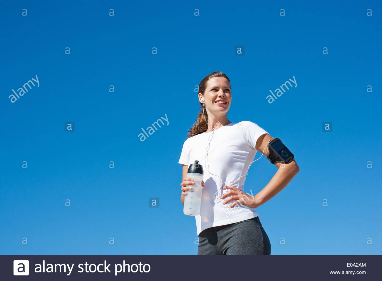 Woman runner drinking from water bottle - Stock Image