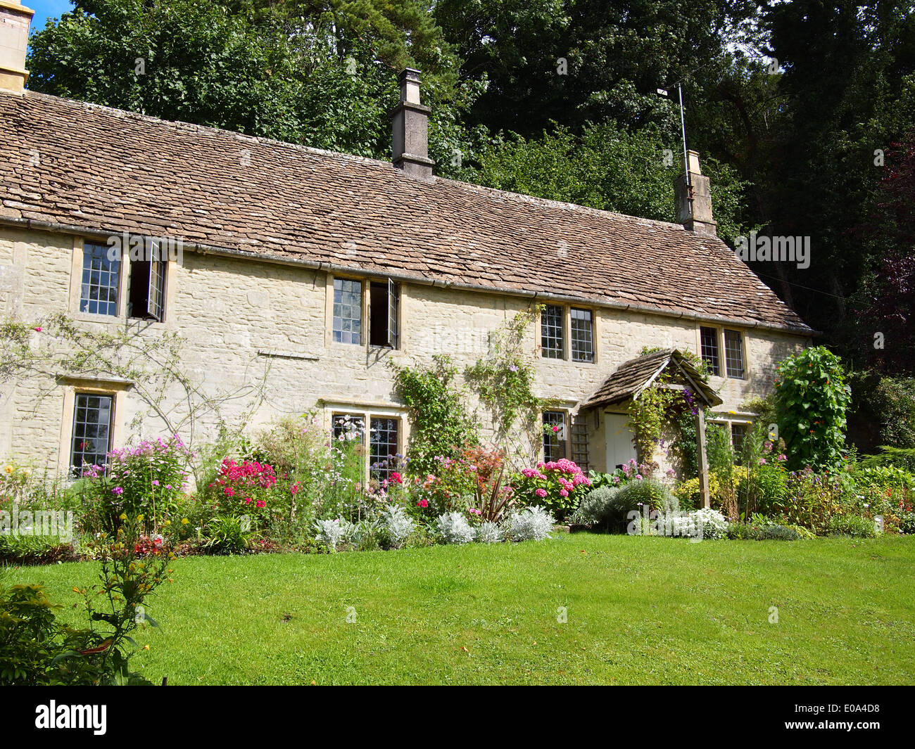 An English cottage built out of Cotswold stone with stone tiles on the roof with a garden full of flowers in the UK. - Stock Image