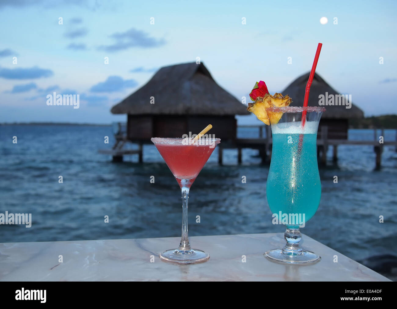 Honeymoon. Two cocktails on a table at dusk with in the background thatched overwater bungalows on a tropical island. - Stock Image