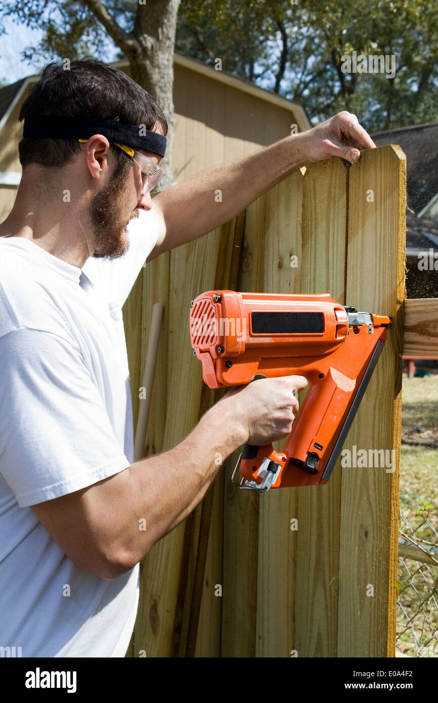 Man wearing safety glasses uses a portable nail gun to attach wood pickets to the rail as he builds a privacy fence. - Stock Image