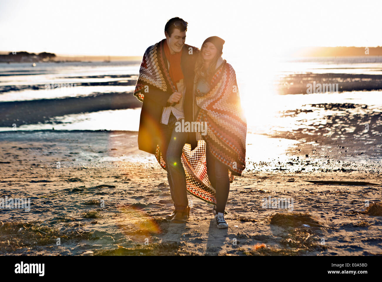 Couple wrapped in a blanket walking on the beach - Stock Image