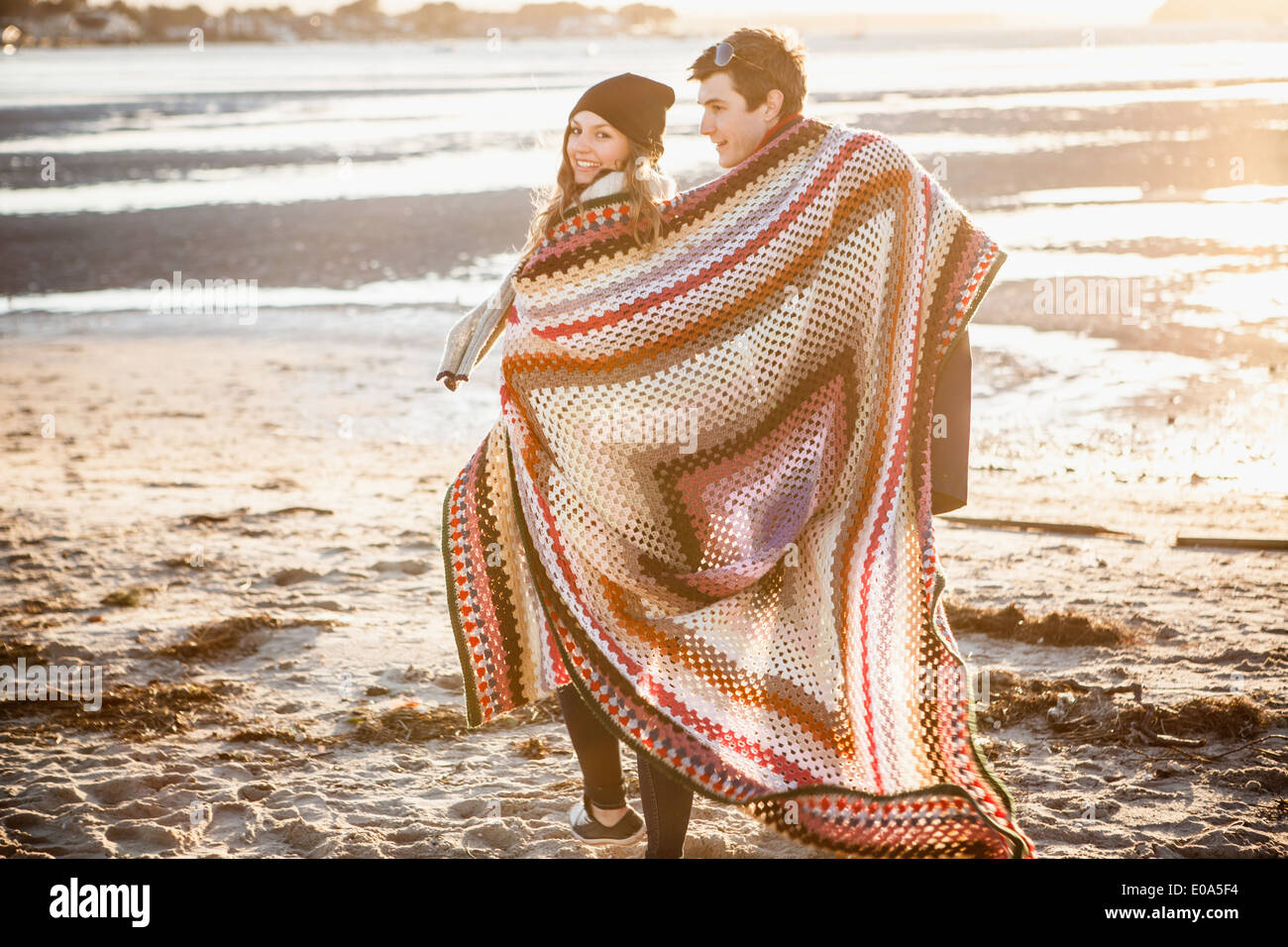 Couple wrapped in a blanket strolling on the beach - Stock Image