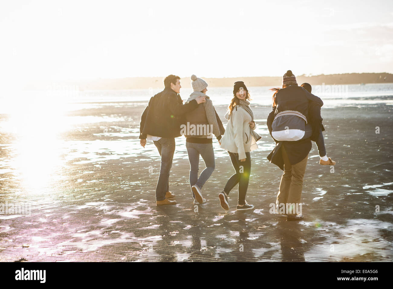 Five adult friends out strolling on the beach - Stock Image