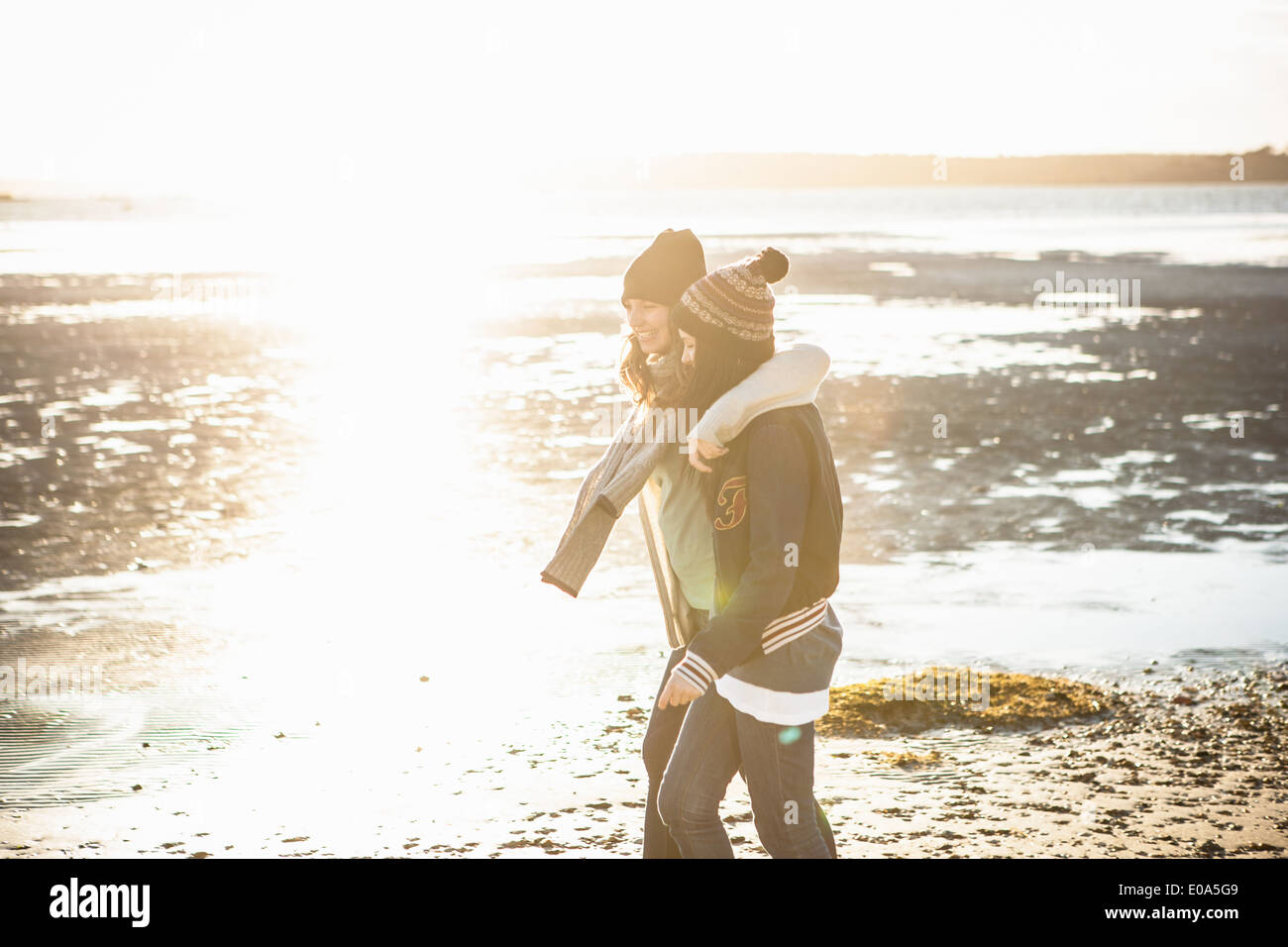 Two young adult female friends strolling on the beach - Stock Image