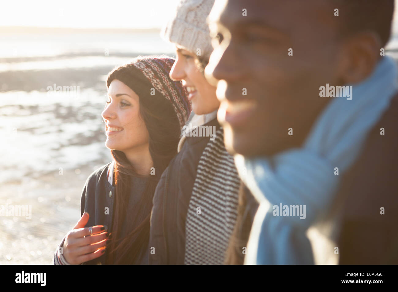Close up of young adult friends strolling on the beach - Stock Image