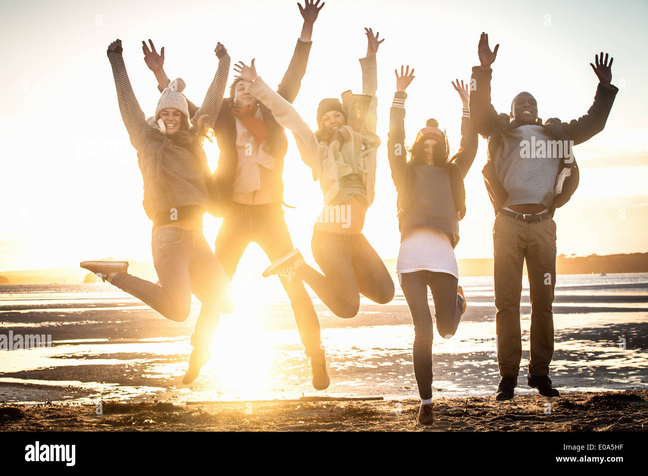 Five adult friends jumping mid air on the beach Stock Photo