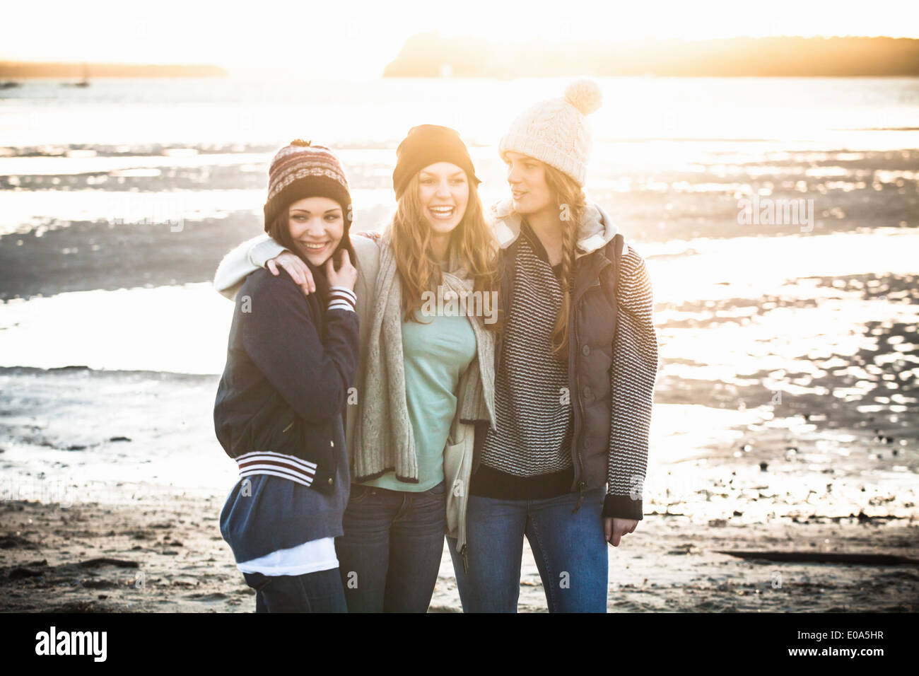 Portrait of three young adult women on the beach - Stock Image