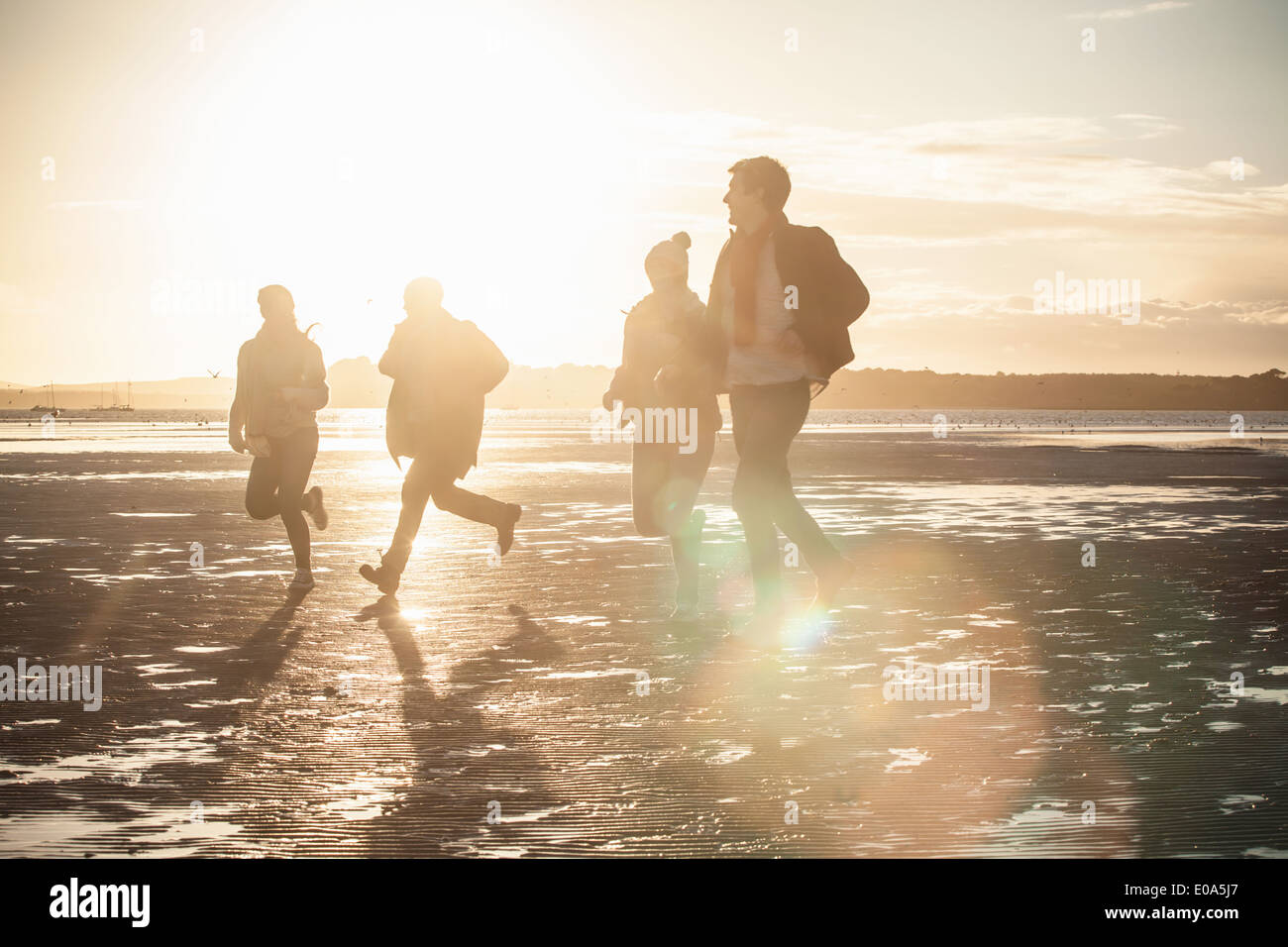 Adult friends racing each other on the beach - Stock Image