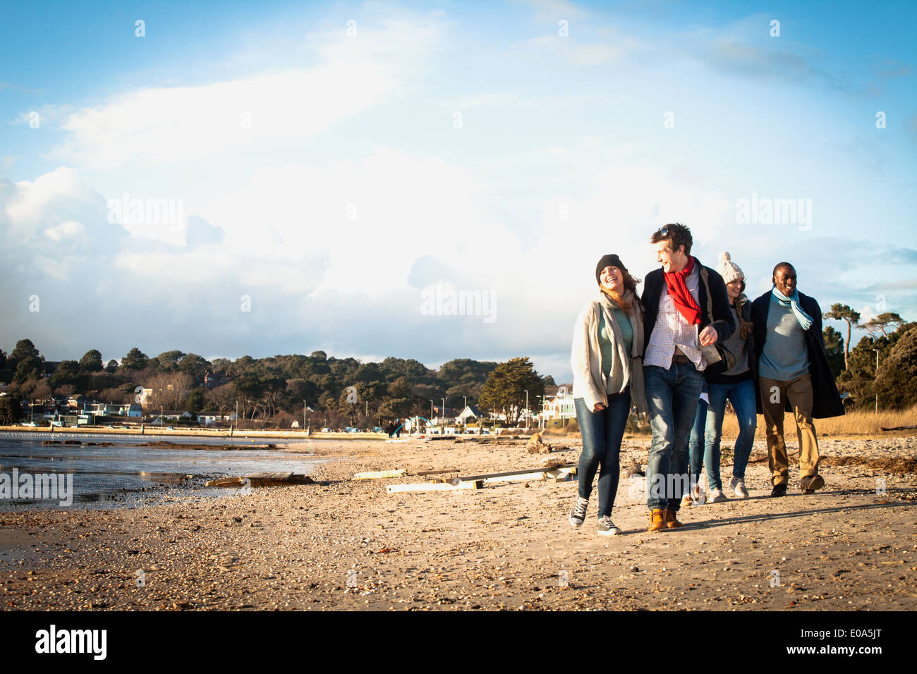 Five adult friends out walking on the beach - Stock Image