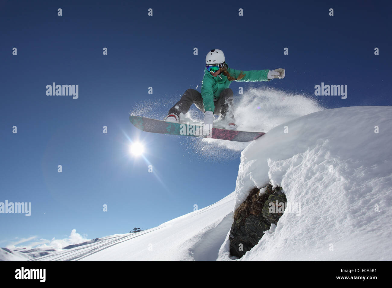 Young woman jumping with snowboard, Mayrhofen, Tyrol, Austria - Stock Image