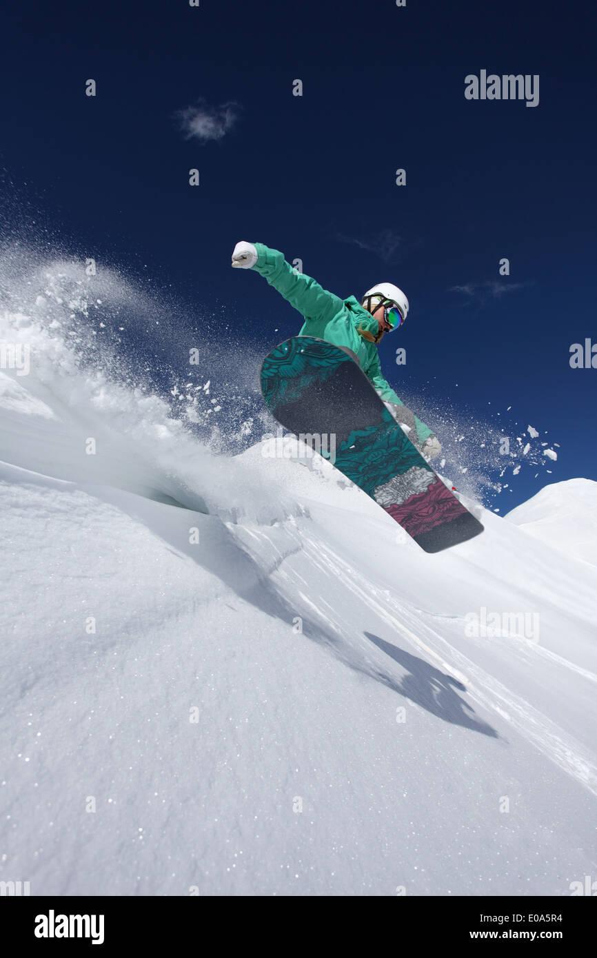 Young woman snowboarding, Mayrhofen, Tyrol, Austria Stock Photo
