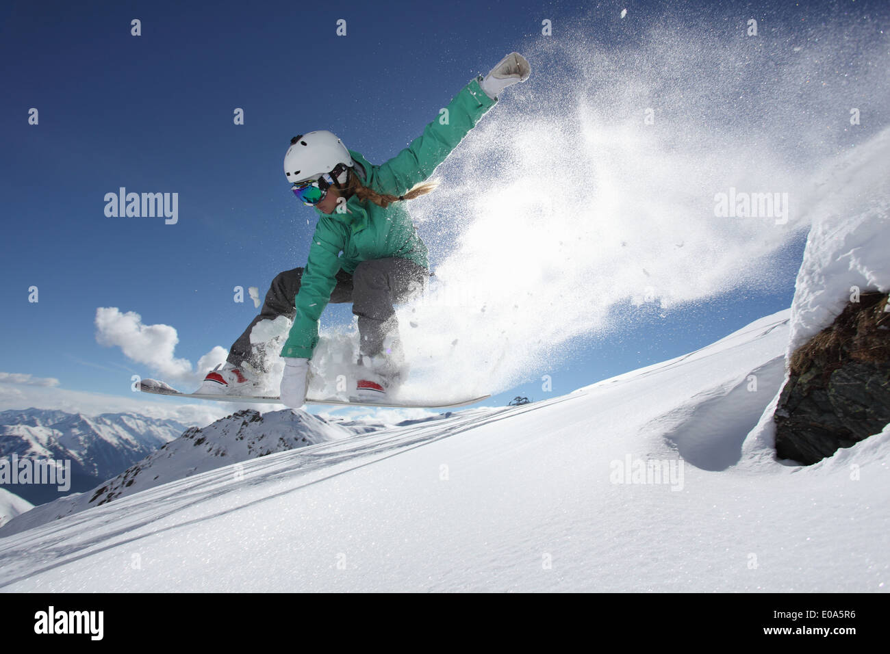 Young woman jumping on snowboard, Mayrhofen, Tyrol, Austria - Stock Image
