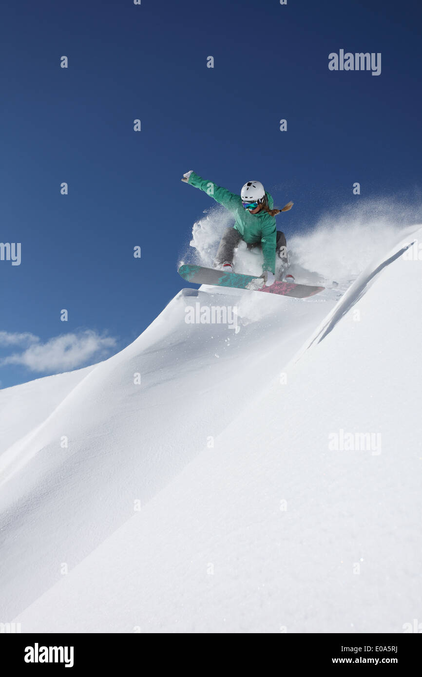 Young woman snowboarding on steep slope, Mayrhofen, Tyrol, Austria Stock Photo
