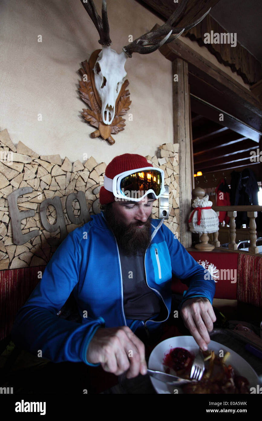 Mid adult male skier enjoying restaurant meal, Tyrol, Austria - Stock Image
