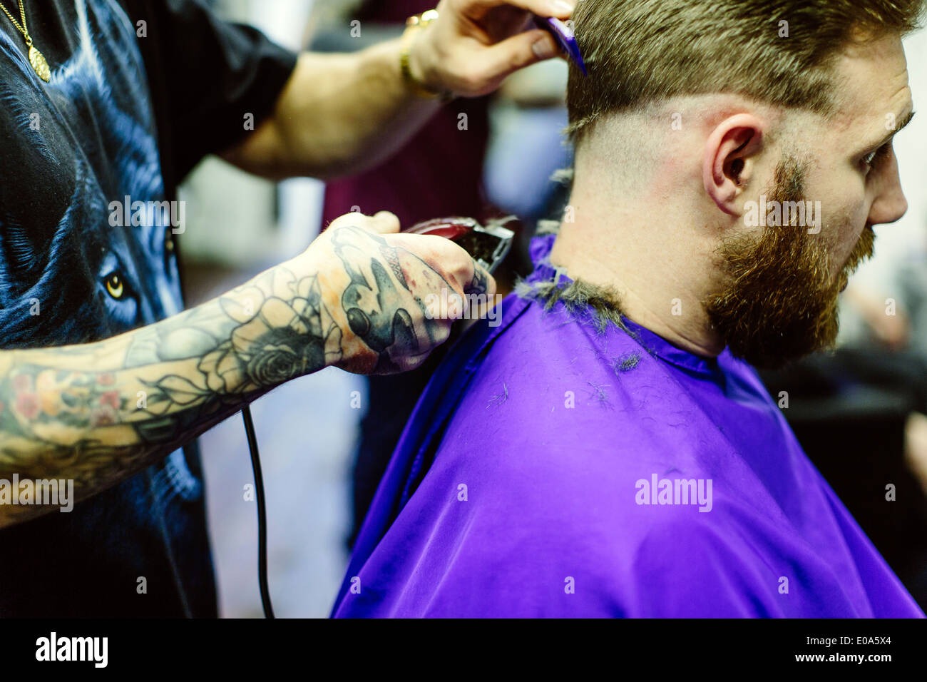 Close up of barber clipping clients hair - Stock Image