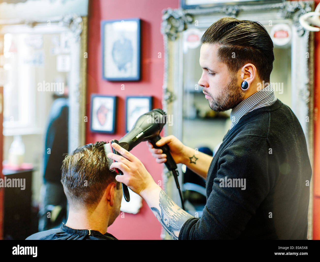Barber blow drying clients hair - Stock Image