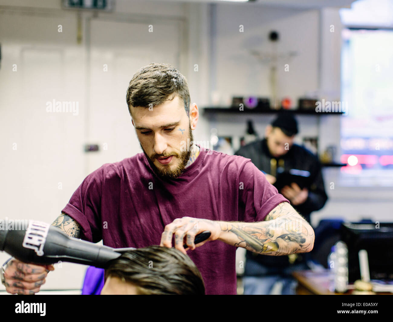Barber blow drying young mans hair - Stock Image
