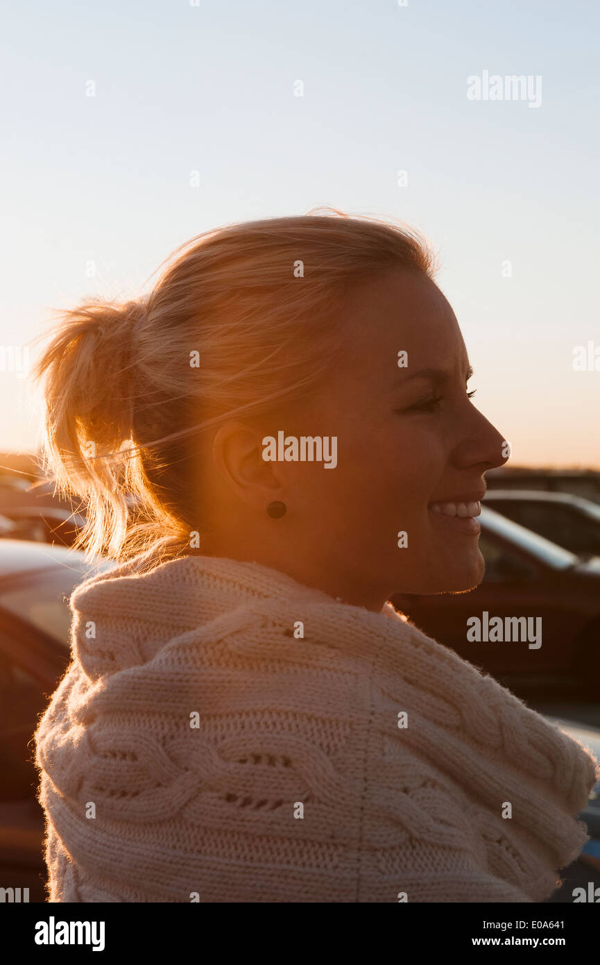 Smiling mid adult woman in parking lot at sunset - Stock Image