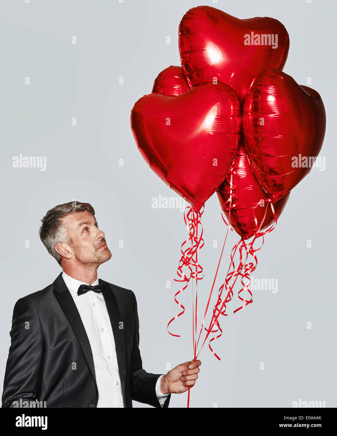 Portrait of man in tuxedo with heart-shaped balloons - Stock Image