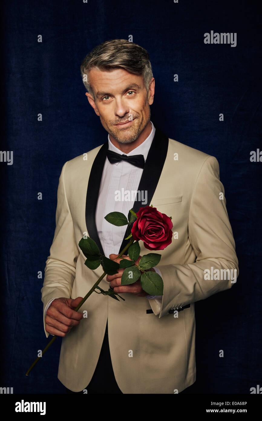 Man in tuxedo holding single rose - Stock Image