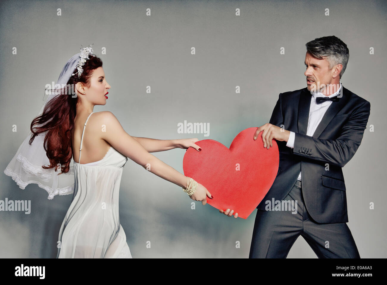 Bride and bridegroom fighting over heart - Stock Image