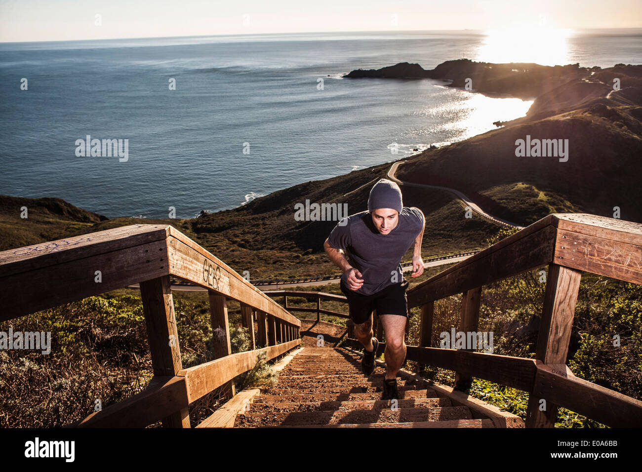 Young man running up coastal staircase at sunset Stock Photo