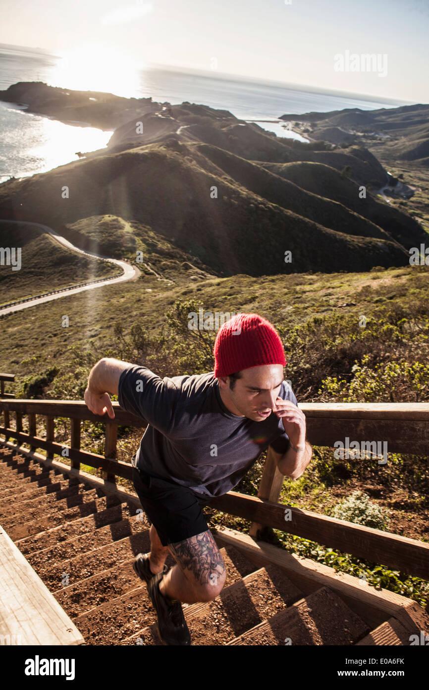 Young man running up coastal staircase - Stock Image