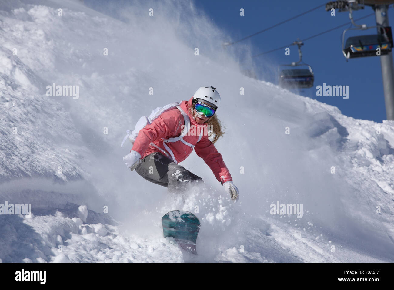 Young woman snowboarding on steep mountain, Hintertux, Tyrol, Austria - Stock Image