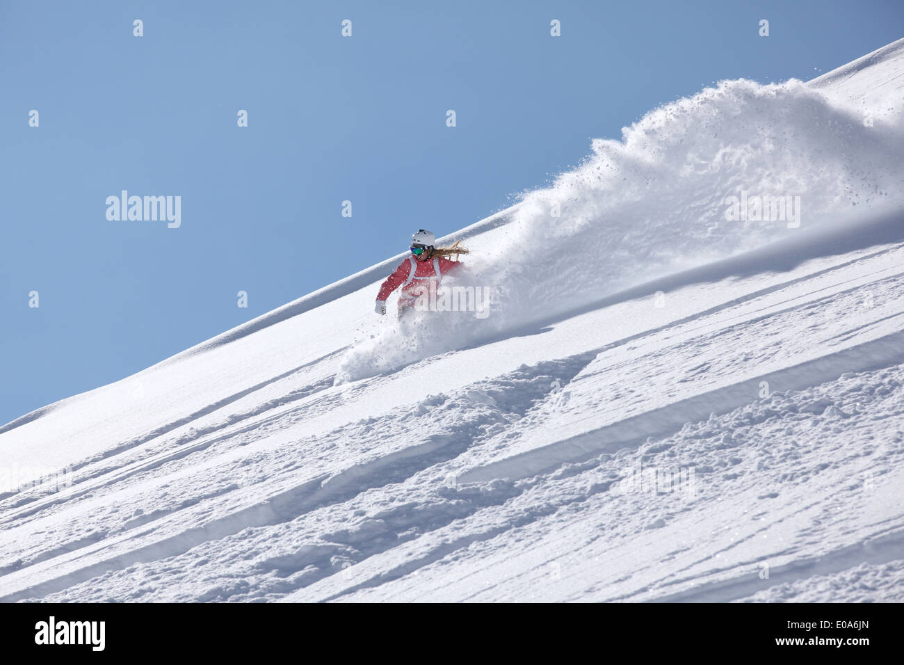 Young woman snowboarding down steep mountain, Hintertux, Tyrol, Austria - Stock Image