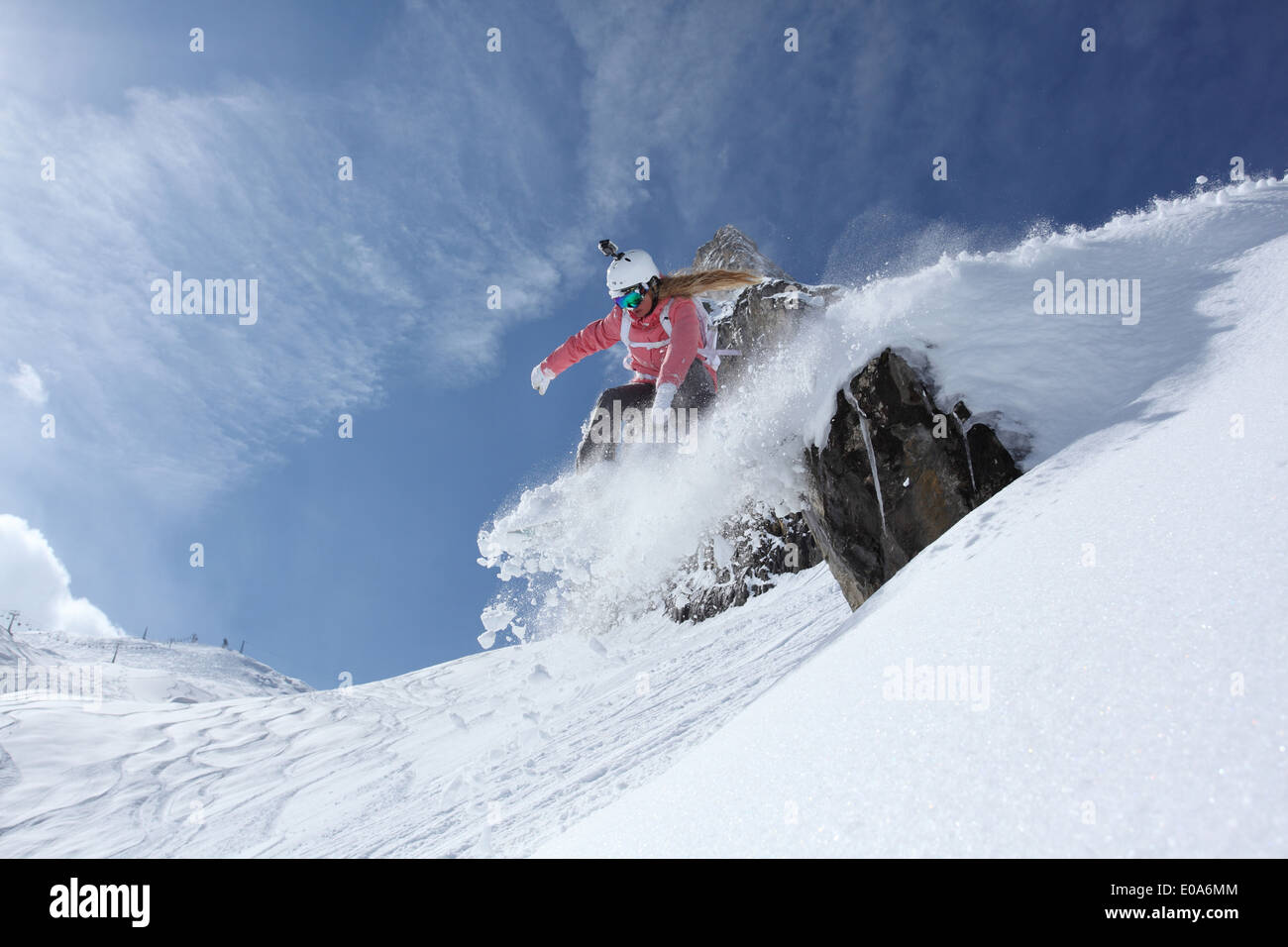 Young female snowboarder jumping off ledge on mountain, Hintertux, Tyrol, Austria - Stock Image