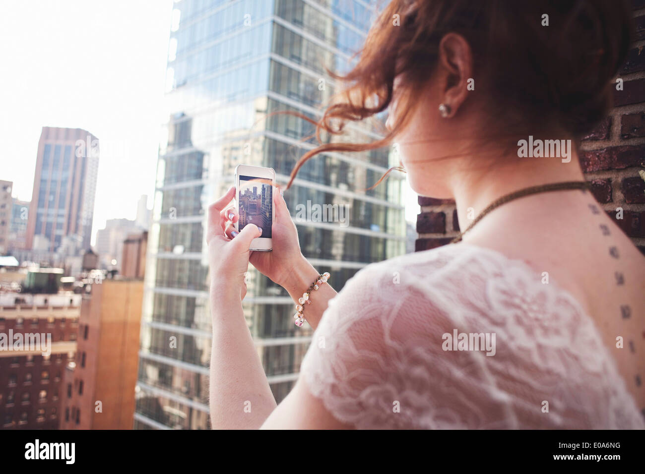 Young woman using smartphone to photograph Manhattan, New York City - Stock Image