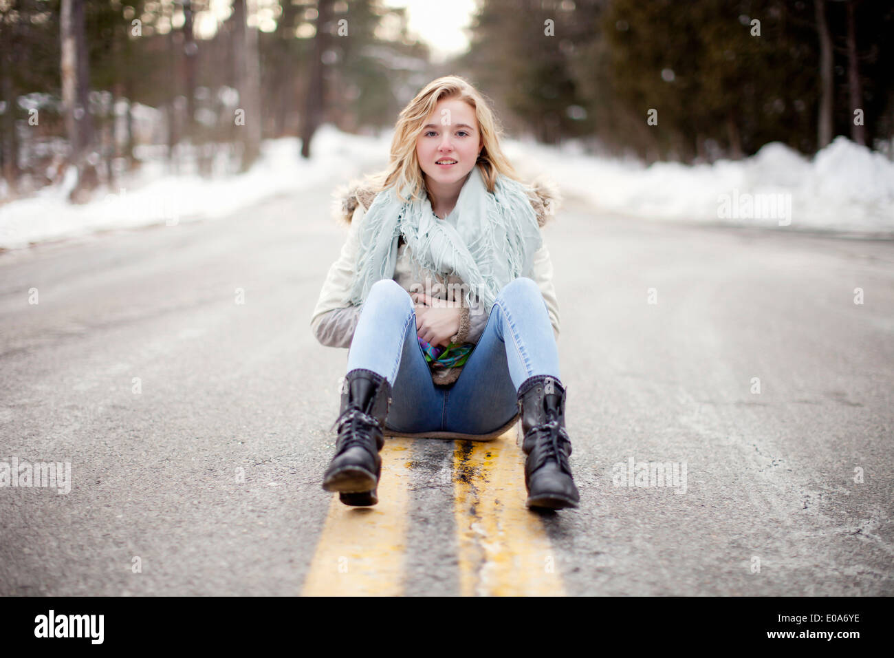 Young woman sitting on road through forest - Stock Image