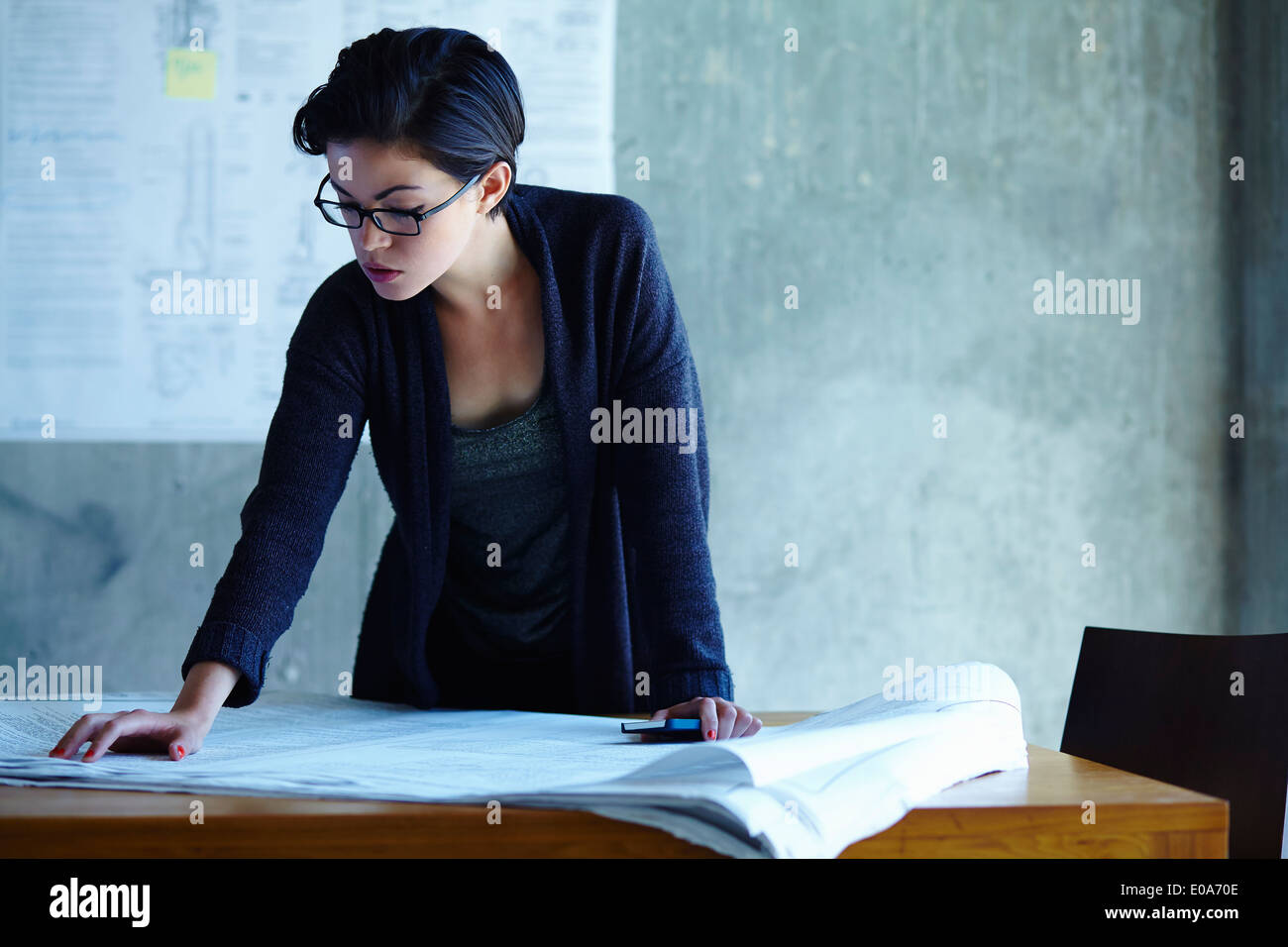 Businesswoman studying blueprints in office - Stock Image