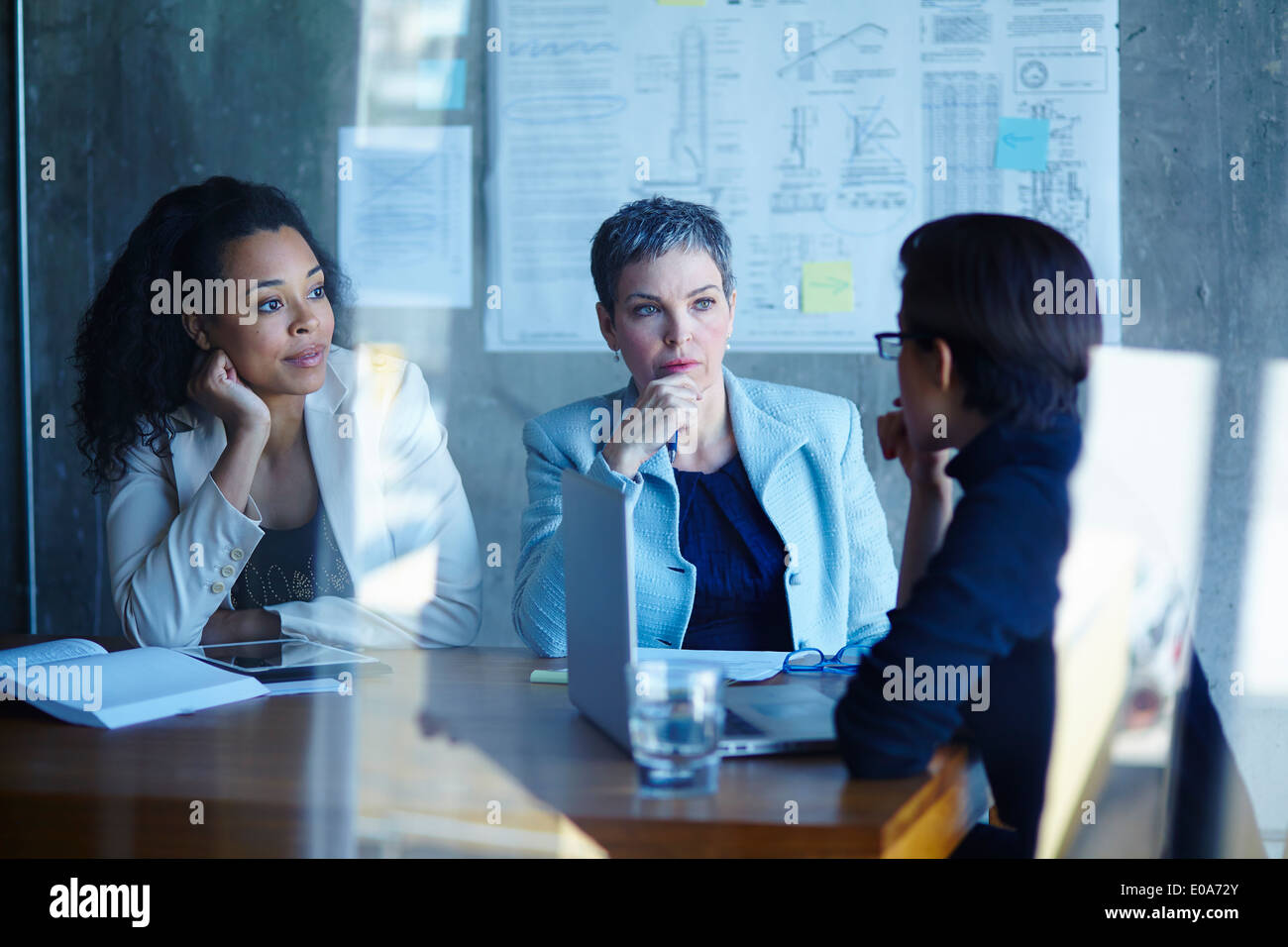 Three businesswomen discussing ideas in boardroom - Stock Image