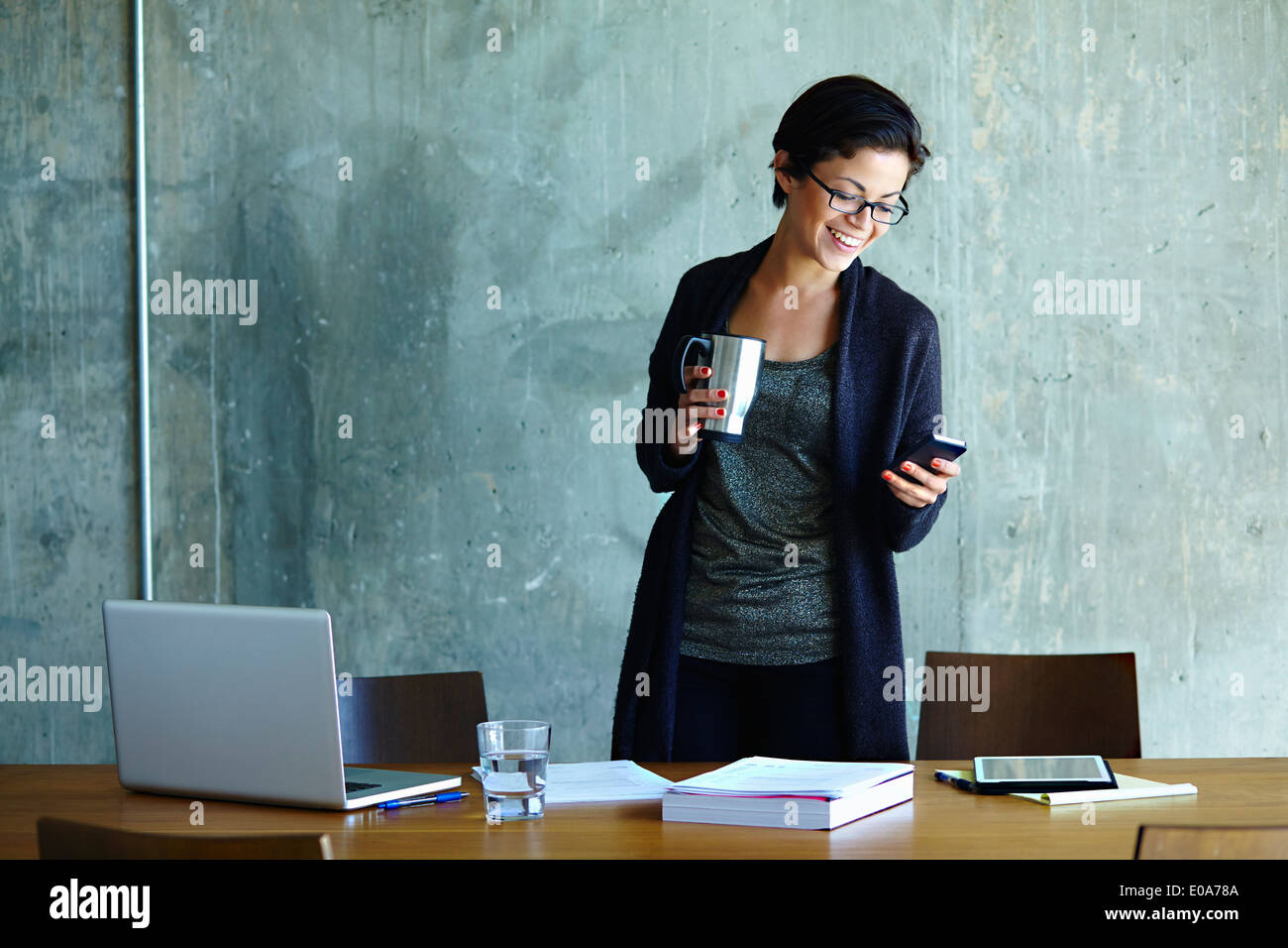 Young businesswoman looking at smartphone in office - Stock Image