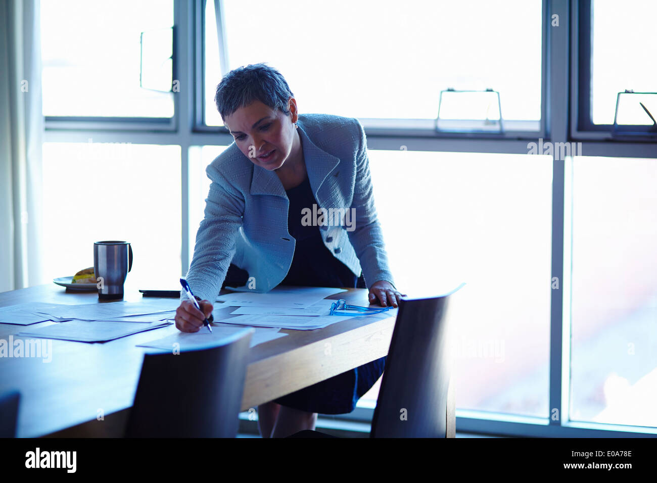 Mature businesswoman at conference table checking papers - Stock Image