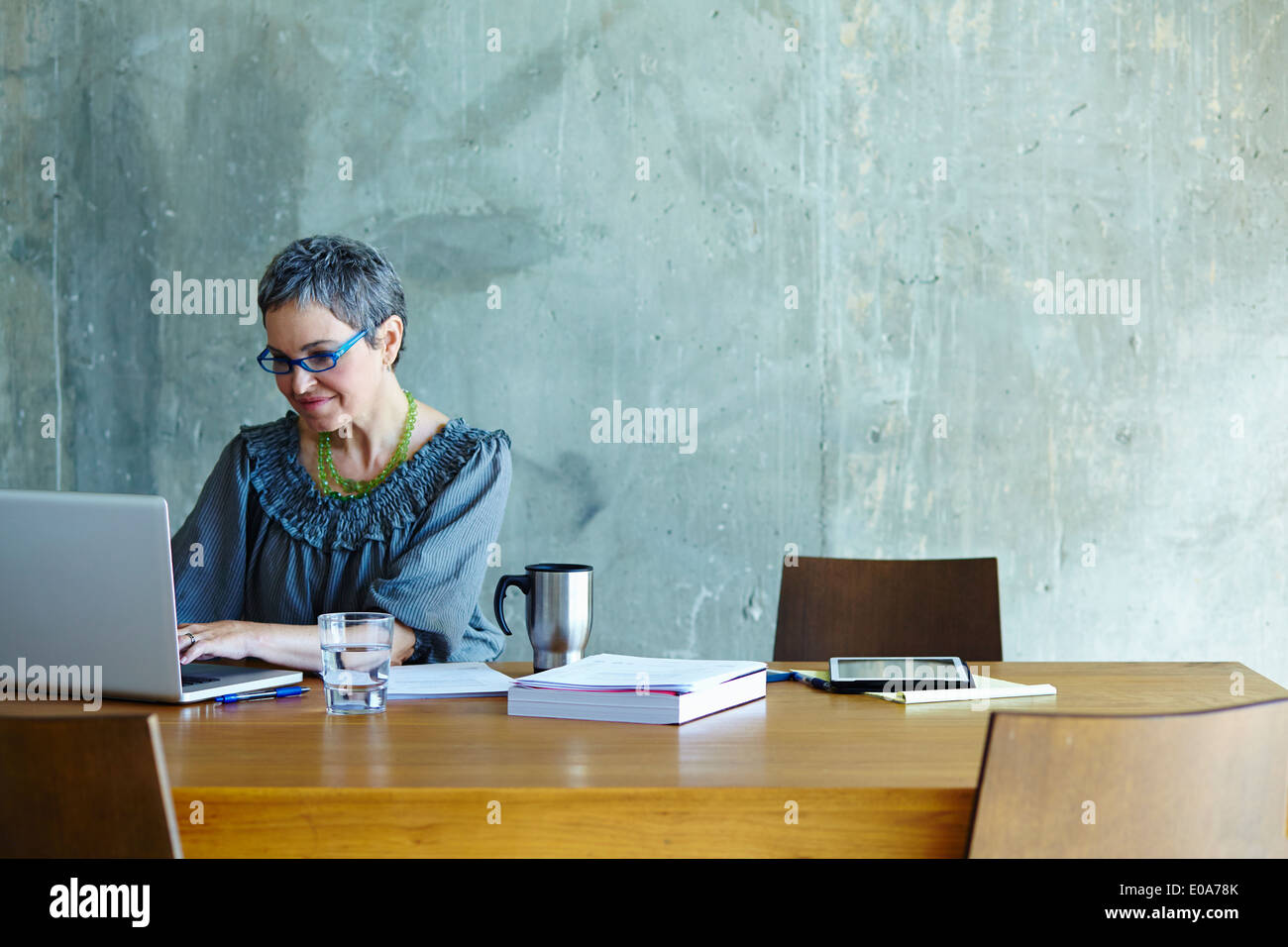 Mature businesswoman at conference table working on laptop - Stock Image