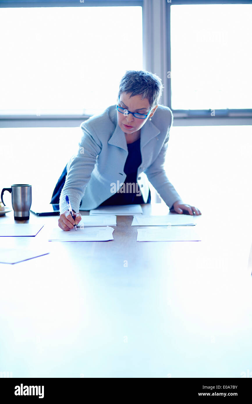 Mature businesswoman at conference table organizing papers - Stock Image