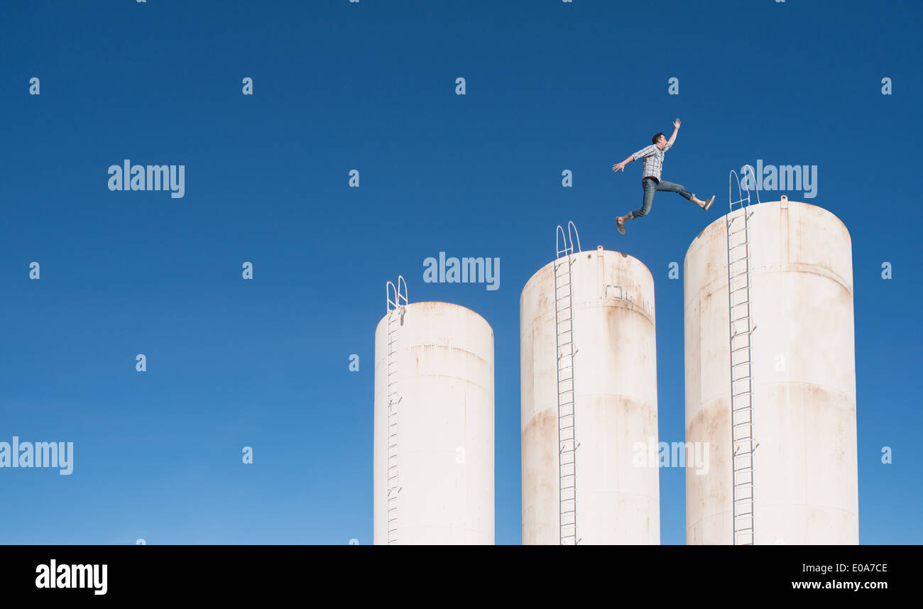 Man leaping across towers - Stock Image
