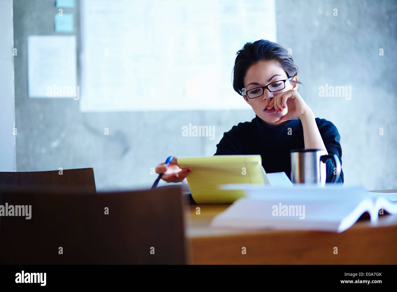 Young businesswomen studying paperwork in office - Stock Image