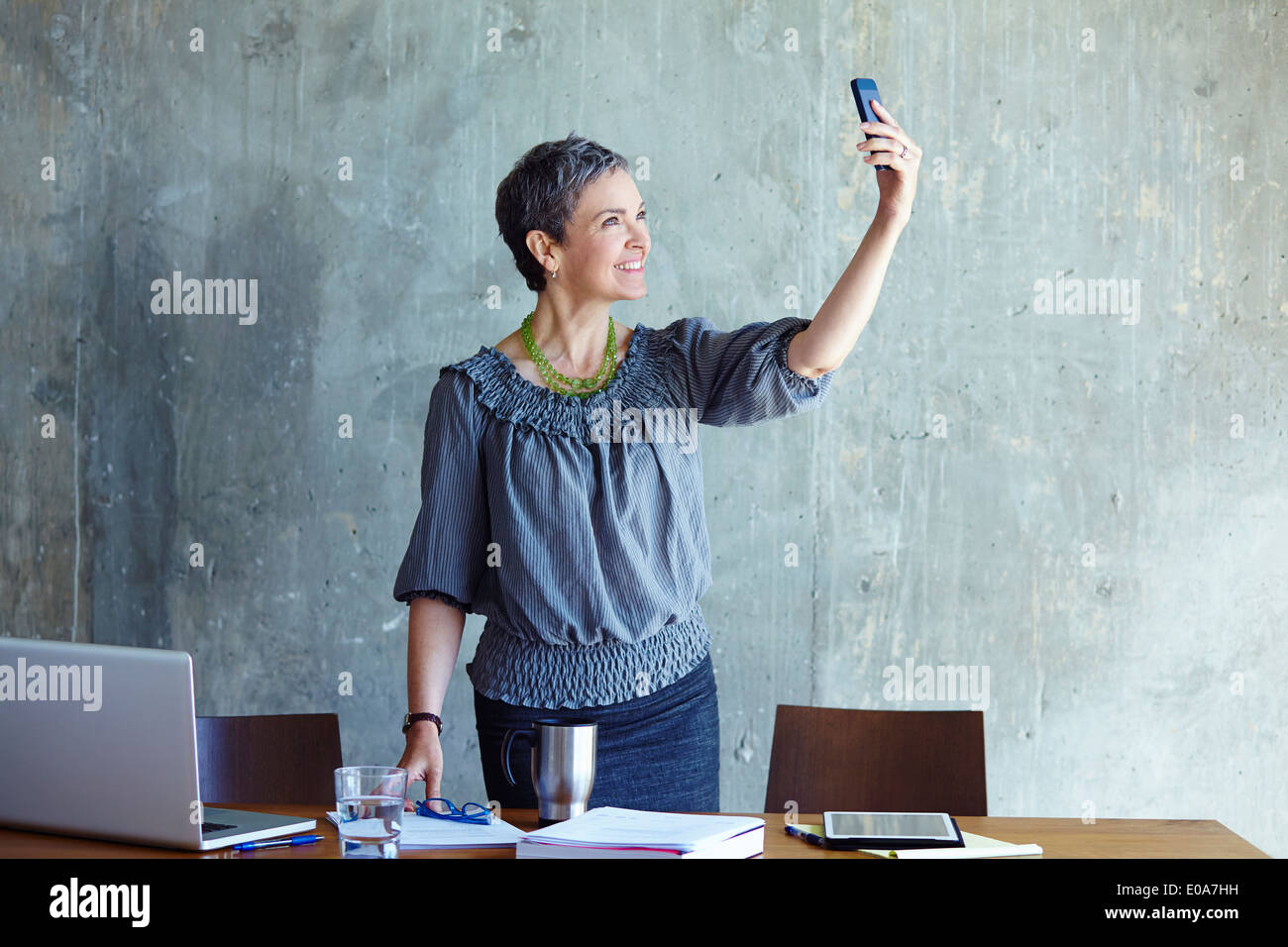 Mature businesswoman taking self portrait in office - Stock Image