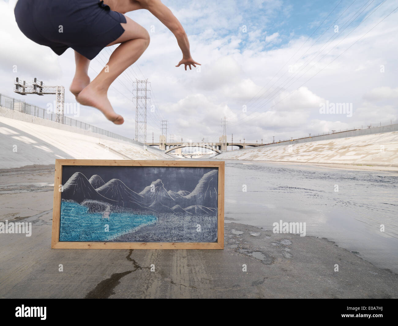 Man pretending to jump into lake, Los Angeles River, Los Angeles, California, USA - Stock Image