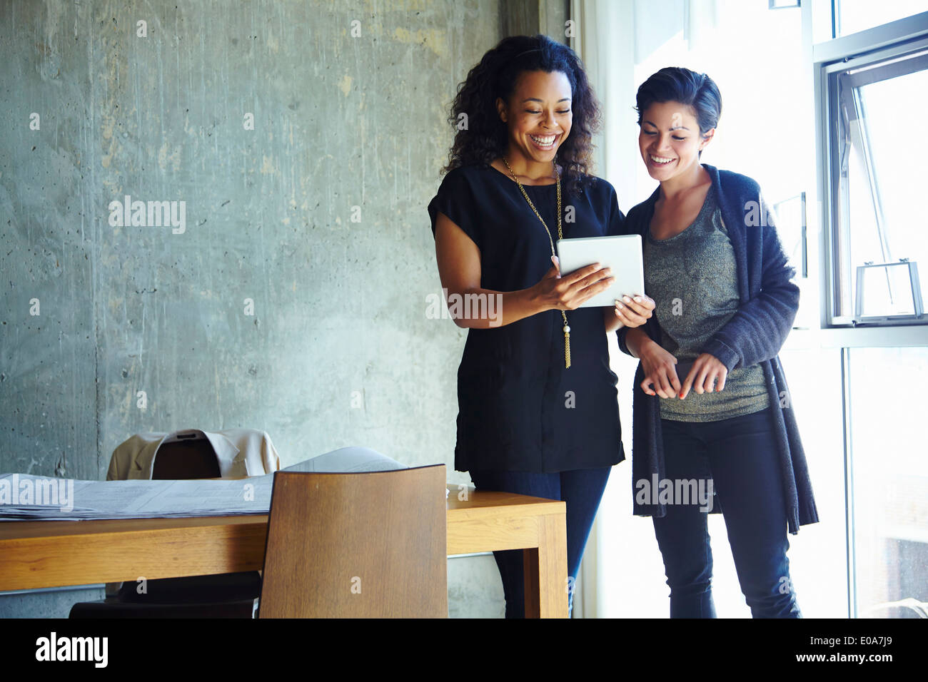 Two young businesswomen looking at digital tablet - Stock Image