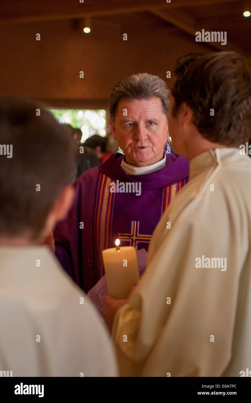 A robed Catholic priest talks with his altar boys before celebrating mass in Laguna Niguel, CA. - Stock Image