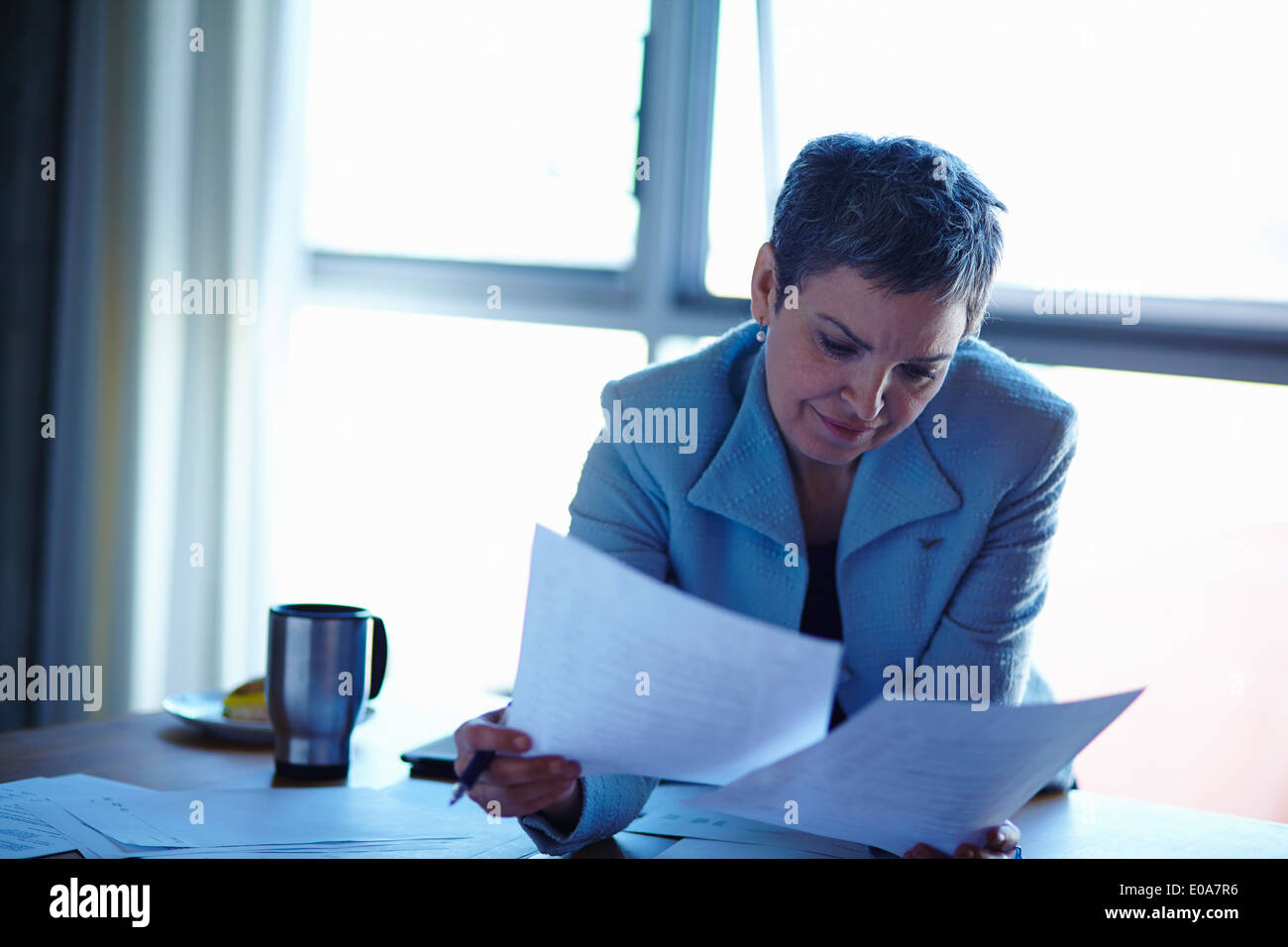 Mature businesswoman reading paperwork in office - Stock Image