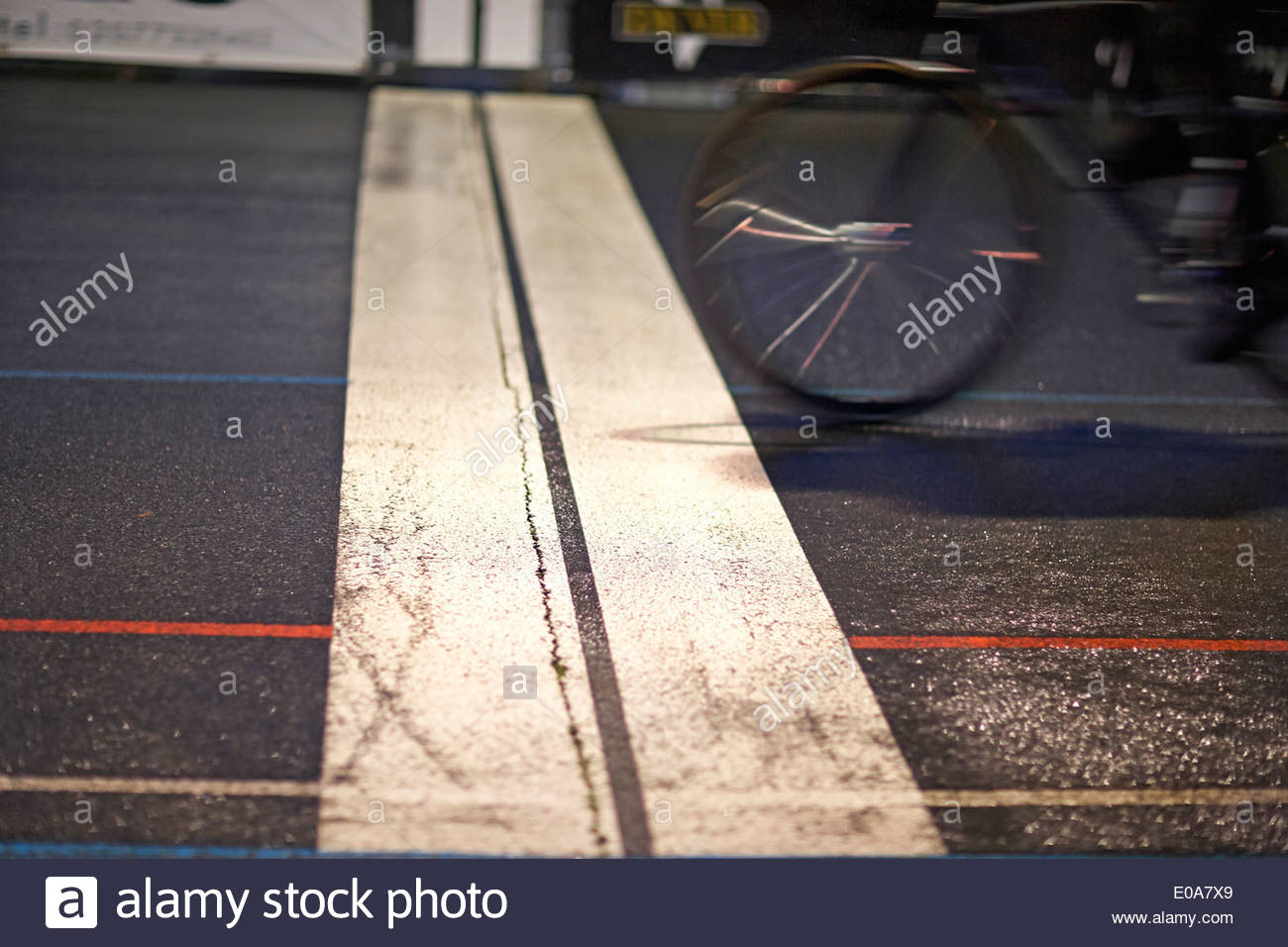 Close up of cyclist racing over finishing line at velodrome - Stock Image