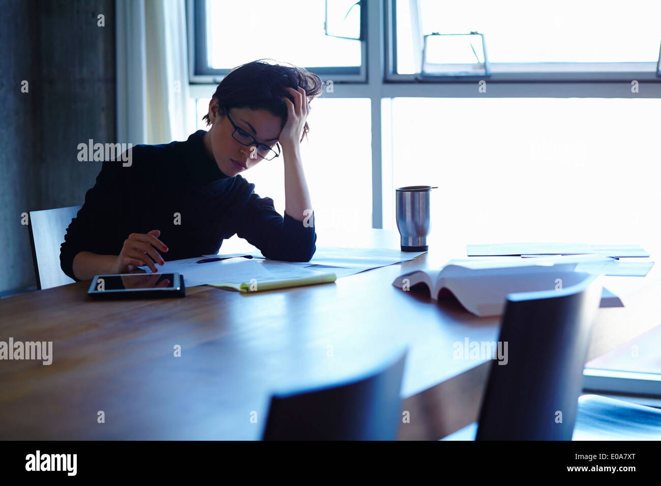 Young businesswomen stressed with paperwork in office - Stock Image