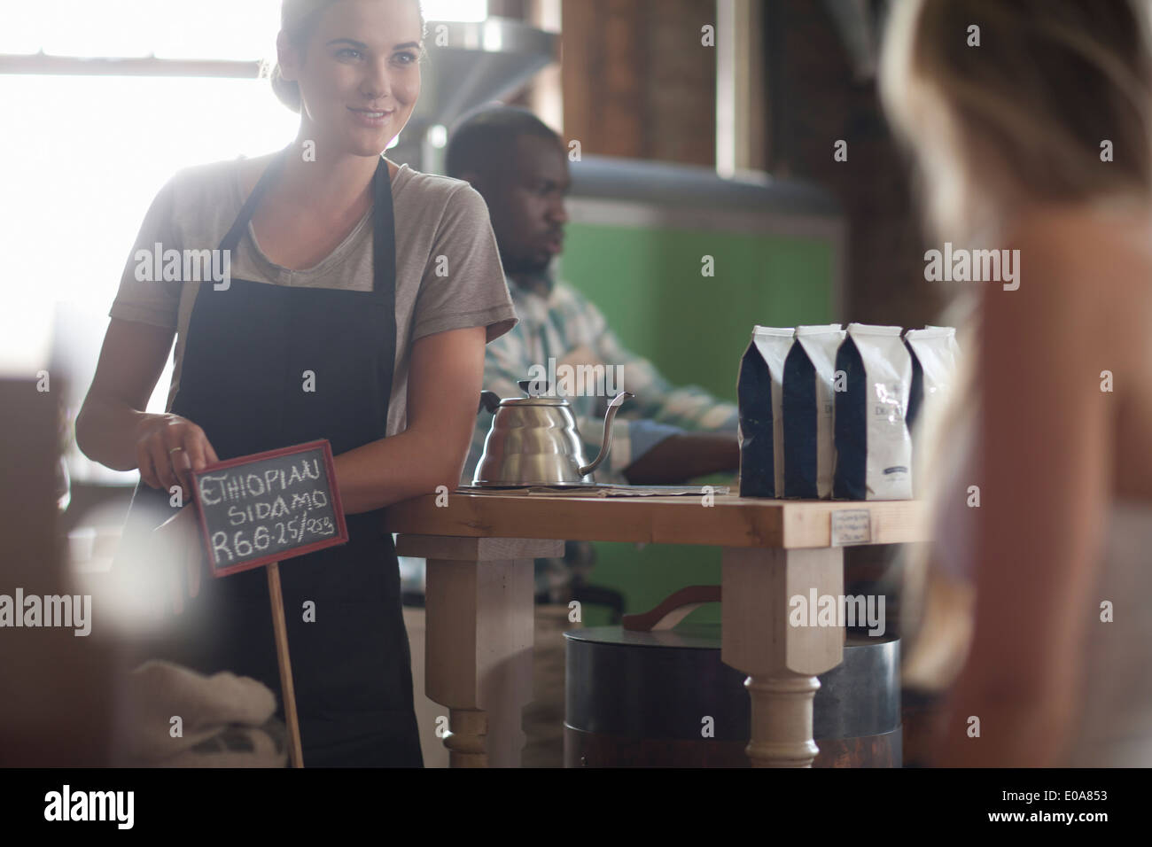 Young female waitress advising on coffee choice in cafe - Stock Image