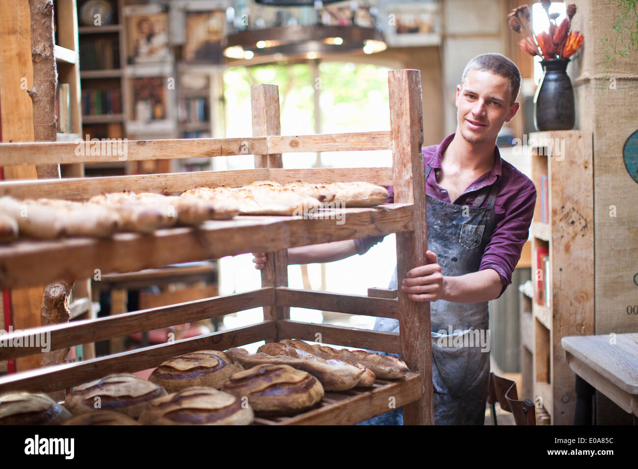 Portrait of young male baker with shelves of fresh bread - Stock Image
