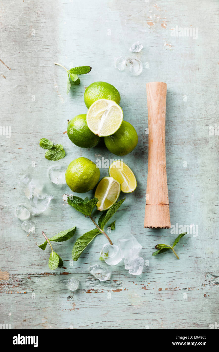 Ingredients for making mojitos Ice cubes, mint leaves and lime on blue background - Stock Image